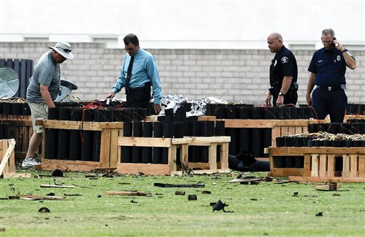 Police officials investigate a site in Simi Valley, Calif., Friday where an explosion Thursday injured more than two dozen people at a fireworks display. The explosion occurred when a wood platform holding live fireworks tipped over, sending the pyrotechnics into the crowd of spectators.