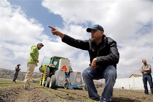 Jorge Heraud, CEO of Blue River Technology, center, explains how the Lettuce Bot works as software engineer Willy Pell, in green, watches in Salinas, Calif., recently. The Lettuce Bot is designed to thin fields of lettuce, a job that now requires detailed hand work by 20 farm workers.