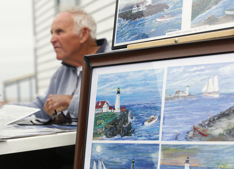 Bill Thomson of Kennebunk sells his paintings of Portland Head Light at Fort Williams Park on Tuesday, July 9, 2013.