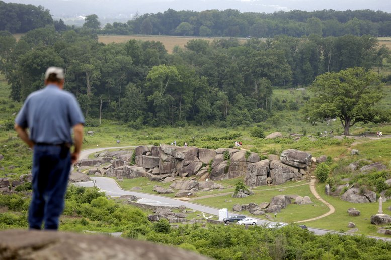Tim Jenkins of Virginia views the Devil's Den from Little Round Top during ongoing activities commemorating the 150th anniversary of the Battle of Gettysburg on Monday in Gettysburg, Pa.