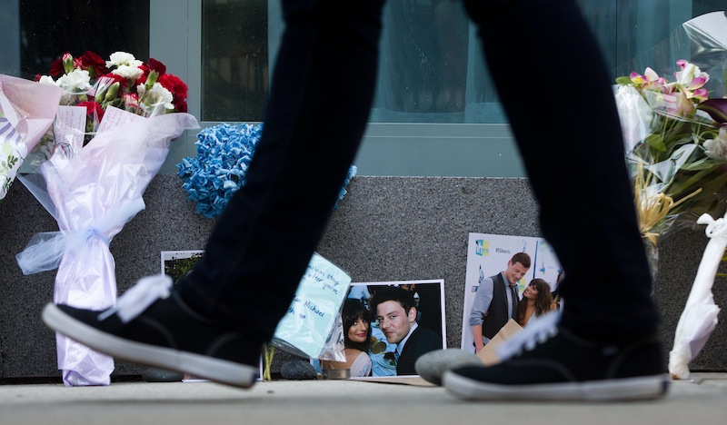 A pedestrian walks past photographs and flowers placed at a memorial for Canadian actor Cory Monteith outside the Fairmont Pacific Rim Hotel in Vancouver, British Columbia on Monday, July 15, 2013. Monteith, 31, was found dead in his room at the hotel on Saturday, according to police, who have ruled out foul play. (AP Photo/The Canadian Press, Darryl Dyck) CANADA;CANADIAN;BRITISH COLUMBIA;B.C.;VANCOUVER;CPPIXBC;CPPIXVANCOUVER;CPPIXBRITISHCOLUMBIA