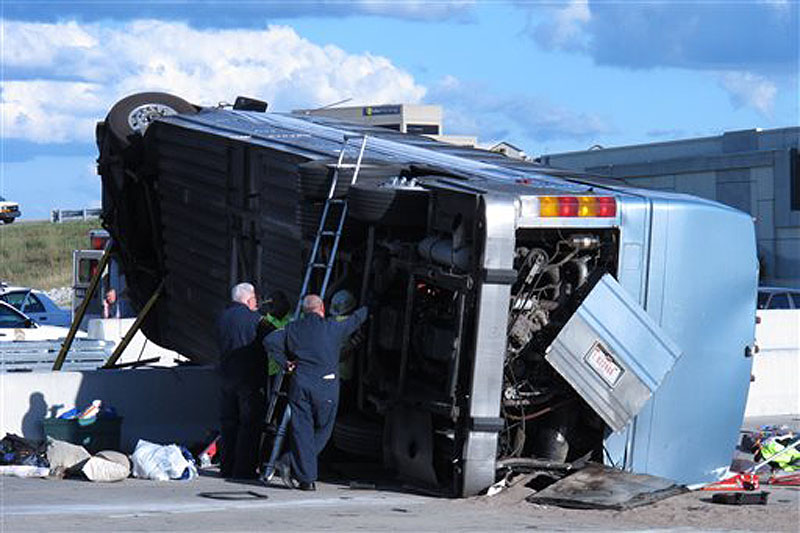 Indiana State Police investigators inspect the underside of a bus that crashed Saturday on the north side of Indianapolis while carrying teenagers returning from a summer camp in Michigan. Three people were killed and 26 others were taken to local hospitals.