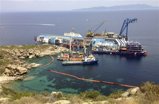 The Costa Concordia cruise ship lies on its side in the waters of the Tuscan island of Giglio, Italy, on Monday. The luxury cruise ship ran aground off the coast of Tuscany on Jan 13, 2012, sending water pouring in through a 160-foot gash in the hull and forcing the evacuation of some 4,200 people from the listing vessel.