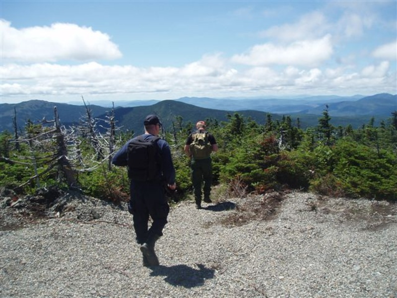 Sgt. Jeff Spencer and Maine State Police Detective Lenny Bolton hike toward Spaulding Mountain from the summit of Sugarloaf as part of the search for missing hiker Geraldine Largay on Saturday.