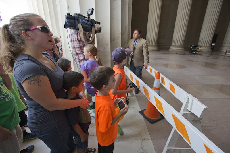 Tourists and reporters stand behind a police barrier as the central hall of the Lincoln Memorial in Washington, Friday, July 26, 2013, as it was closed for cleaning after someone splattered green paint on the statue of the 16th president and the floor area. Police say the apparent vandalism was discovered early Friday morning with no words, letters or symbols visible in the paint. (AP Photo/J. Scott Applewhite)