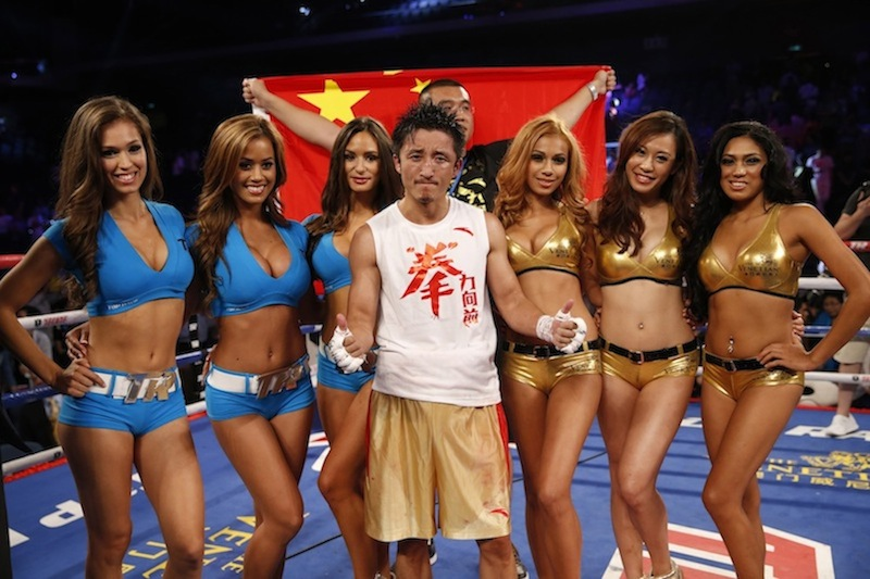 Chinese boxer Zou Shiming poses with ring girls before the Flyweight Bout match against Mexico's Jesus Ortega at the Cotai Arena in Venetian Macao in Macau Saturday July 27, 2013.A Chinese fighter's victory at a Macau showdown brings the world's top casino market a step closer to challenging Las Vegas for dominance of another Sin City staple: big-time boxing matches. Macau, which long ago eclipsed Vegas as the world's top gambling city, is now looking to add to its allure by holding the kind of boxing bouts that Las Vegas is known for. (AP Photo/Dennis Ho)