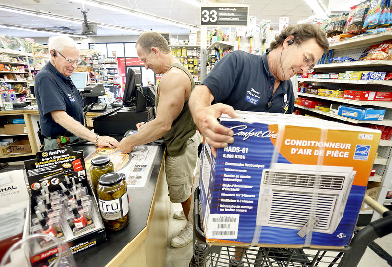 Gary F. Smith loads an air conditioner into a shopping cart for customer Mark Flowers of Scarborough, middle, while Tap Fitzgerald receives payment at Maine Hardware in Portland on July 16, 2013.