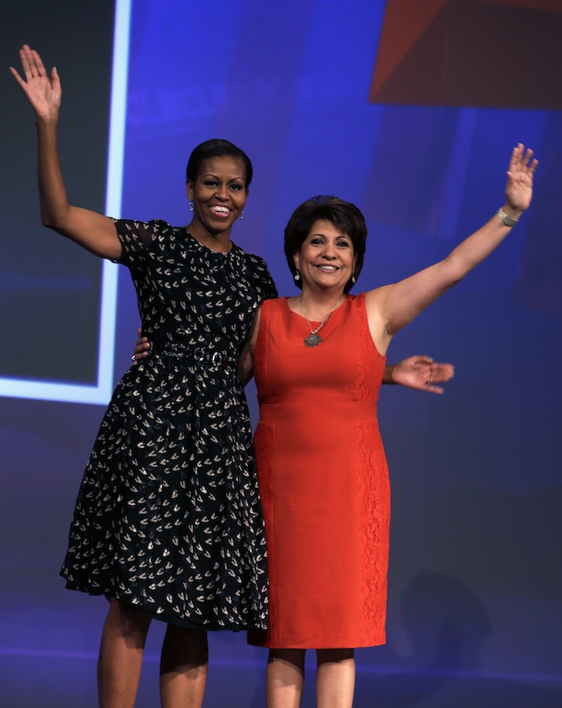 First lady Michelle Obama and National Council of La Raza President Janet Murguia wave as she arrives onstage to speak about childhood obesity, Tuesday, July 23, 2013, at the NCLR annual meeting New Orleans. The conference and a related