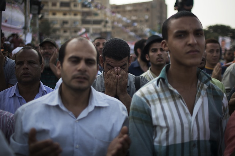 """Supporters of the ousted Egypt's President Mohammed Morsi pray during a protest in Nasr City, a suburb of Cairo, Egypt, Tuesday July 9, 2013. After days of deadlock, Egypt's military-backed interim president named a veteran economist as prime minister on Tuesday and appointed pro-democracy leader Mohamed ElBaradei as a vice president, while the army showed its strong hand in shepherding the process, warning political factions against """"maneuvering"""" that impedes the transition. (AP Photo/Manu Brabo)"""