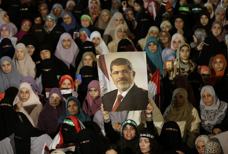 Supporters of the ousted Egypt's President Mohammed Morsi, hold his portrait during a demonstration after the Iftar prayer, evening meal when Muslims break their fast during the Islamic month of Ramadan, in Nasr City, Cairo, Egypt, Wednesday July 10, 2013. Egypt's military-backed government tightened a crackdown on the Muslim Brotherhood on Wednesday, ordering the arrest of its revered leader in a bid to choke off the group's campaign to reinstate President Mohammed Morsi one week after an army-led coup. (AP Photo/Hussein Malla)