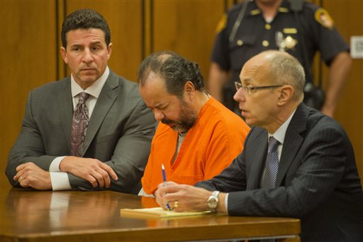 Ariel Castro, center, enters the court before a judge with his defense attorney's, Craig Weintraub, left, and Jaye Schlachet during a pretrial hearing on Wednesday, June 19, 2013, in Cleveland. A tentative Aug. 4 trial date has been set for Castro, accused of kidnapping three women and holding them in his home for about a decade.
