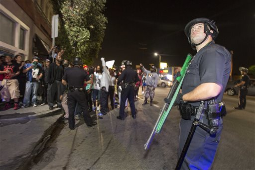 A police officer stands guard as demonstrators march on Crenshaw Boulevard near the I-10 freeway during a protest in Los Angeles on Sunday, July 14, 2013, the day after George Zimmerman was found not guilty in the shooting death of Trayvon Martin. Seventeen-year-old Martin was shot and killed in February 2012 by neighborhood watch volunteer George Zimmerman.