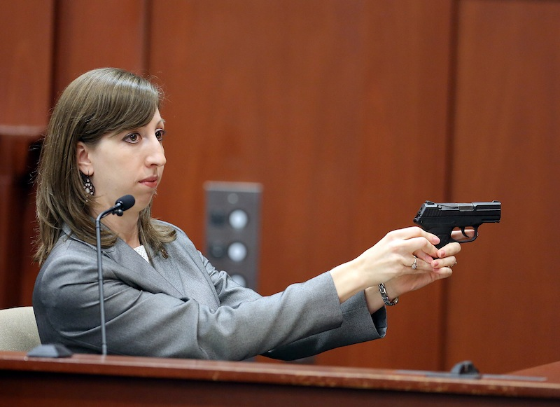 Amy Siewert, a firearms expert with the Florida Department of Law Enforcement, faces the jury as she demonstrates George Zimmerman's gun during the George Zimmerman trial in Seminole circuit court, in Sanford, Fla., Wednesday, July 3, 2013. Zimmerman is charged with second-degree murder in the fatal shooting of Trayvon Martin, an unarmed teen, in 2012. (AP Photo/Orlando Sentinel, Jacob Langston, Pool)
