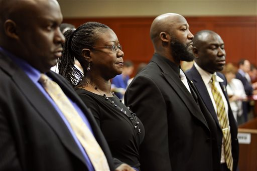 Flanked by attorneys Daryl Parks, left, and Benjamin Crump, far right, Trayvon Martin's parents Sabrina Fulton, second from left, and Tracy Martin, stand during closing arguments in George Zimmerman's trial in Seminole circuit court in Sanford, Fla. Thursday, July 11, 2013. Zimmerman has been charged with second-degree murder for the 2012 shooting death of Trayvon Martin.
