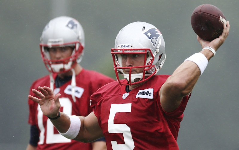 New England Patriots quarterback Tim Tebow, right, throws as starting quarterback Tom Brady looks on during NFL football training camp in Foxborough, Mass., Friday, July 26, 2013. (AP Photo/Charles Krupa). (AP Photo/Charles Krupa)