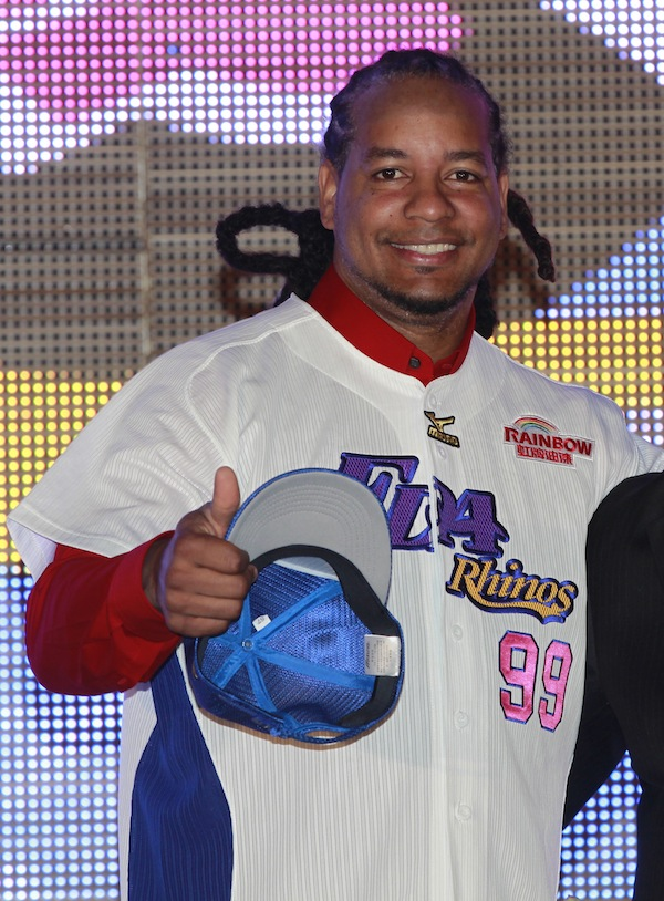 In this March 12, 2013 file photo, former Major League Baseball star Manny Ramirez poses for media wearing his new jersey after signing a short-term contract to play on the EDA Rhinos in Taiwan's professional baseball league, in Kaohsiung, Taiwan. The Texas Rangers have signedRamirez to minor league contract. Ramirez spent three months playing in Taiwan before leaving the team on June 20. The Rangers made the announcement Wednesday, July 3, 2013. (AP Photo/Wally Santana, File)