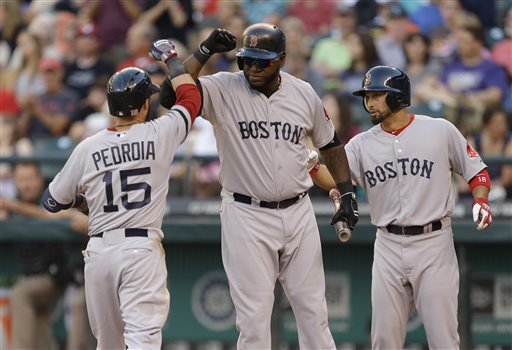 Boston Red Sox's Dustin Pedroia is greeted at the plate by Red Sox's David Ortiz, center, and Shane Victorino, right, after Pedroia hit a solo home run in the third inning of a baseball game against the Seattle Mariners, on Tuesday in Seattle.