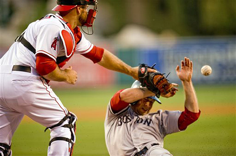Boston's Daniel Nava beats the throw home to Los Angeles Angels catcher Chris Iannetta to score in the second inning Saturday in Anaheim, Calif. The Angels won in the 11th inning, 9-7.