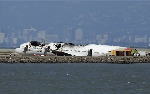 """The wreckage of Asiana Airlines Flight 214 sits on the tarmac in San Francisco. Investigators said the Boeing 777 was traveling """"significantly below"""" the target speed during its approach and that the crew tried to abort the landing just before it smashed onto the runway."""