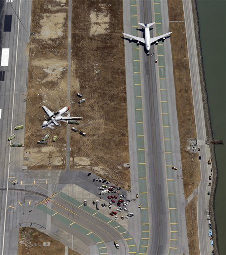 This aerial photo shows a United Airlines plane sitting on the adjacent runway next to the wreckage of the Asiana Flight 214 airplane after it crashed at the San Francisco International Airport in San Francisco, Saturday, July 6, 2013.
