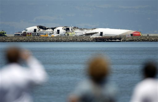 People look at the wreckage of Asiana Flight 214 where it crashed at San Francisco International Airport in San Francisco on Saturday.