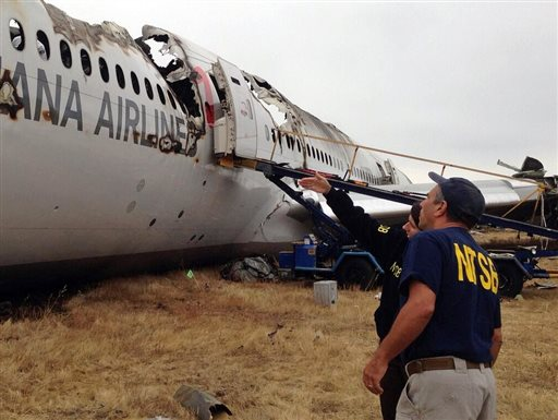 This photo provided by the National Transportation Safety Board, on Tuesday shows Investigator in Charge Bill English, foreground, and Chairman Deborah Hersman discussing the progress of the investigation into the crash of Asiana Airlines Flight 214 in San Francisco.