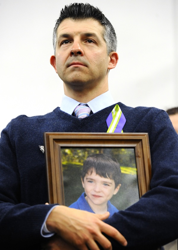 """In this Jan. 14, 2013 file photo, Ian Hockley, father of Sandy Hook School shooting victim Dylan, holds a photo of his son at a news conference at Edmond Town Hall in Newtown, Conn. Some Newtown families have said they were given a voice late in the process of dispersing the millions of dollars in donated funds, and that the process has been bureaucratic, difficult, unpleasant, and has added to their pain. """"What's the objective here?"""" Hockley said. """"The objective is to heal Newtown and to take care of its most affected people."""" (AP Photo/Jessica Hill, File)"""