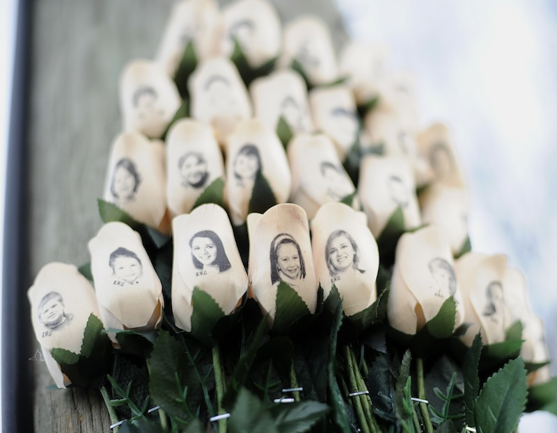 In this Jan. 14, 2013 file photo, white roses with the faces of victims of the Sandy Hook Elementary School shooting are attached to a telephone pole near the school on the one-month anniversary of the shooting that left 26 dead in Newtown, Conn. Some Newtown families have said they were given a voice late in the process of dispersing the millions of dollars in donated funds, and that the process has been bureaucratic, difficult, unpleasant, and has added to their pain. (AP Photo/Jessica Hill, File)