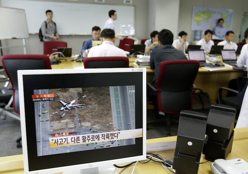 A screen showing a news program reporting about Asiana Airlines flight 214 which took off from Seoul and crashed while landing at San Francisco International Airport as employees of Asiana Airlines work at Crisis Management Center of Asiana Airlines head office in Seoul, South Korea, Sunday, July 7, 2013. (AP Photo/Lee Jin-man, Pool)