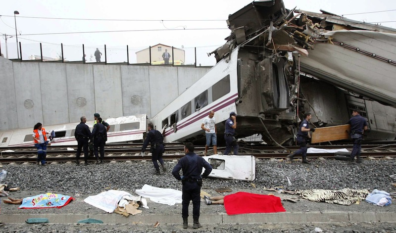 Emergency personnel respond to the scene of a train derailment in Santiago de Compostela, Spain, on Wednesday, July 24, 2013, where bodies are covered by towels. The train, carrying 218 passengers in eight carriages, hurtled off the tracks and slammed into a concrete wall, killing 79 people. (AP Photo/ El correo Gallego/Antonio Hernandez)