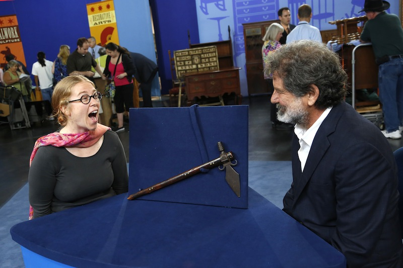 """This June 22, 2013 photo released by PBS shows Ted Trotta, of Trotta-Bono, Ltd., right, looking at Lisa as she reacts about information about her Spontoon Tomahawk Pipe during the taping of the popular appraisal show """"Antiques Roadshow,"""" in Anaheim, Calif. Top-rated PBS series """"Antiques Roadshow"""" is on the move, taping programs in eight U.S. cities for its upcoming 18th season. (AP Photo/PBS)"""