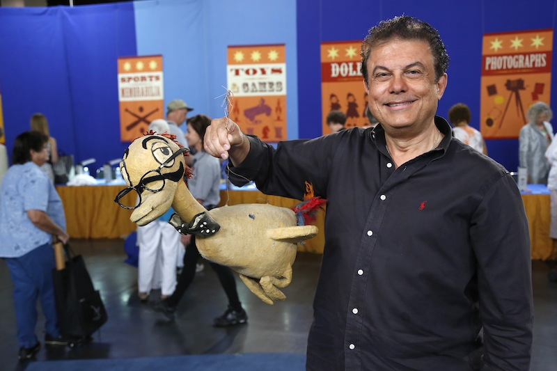 This June 22, 2013 photo released by PBS shows a man named Joe holding a Max Brother prop duck during the taping of the popular appraisal show
