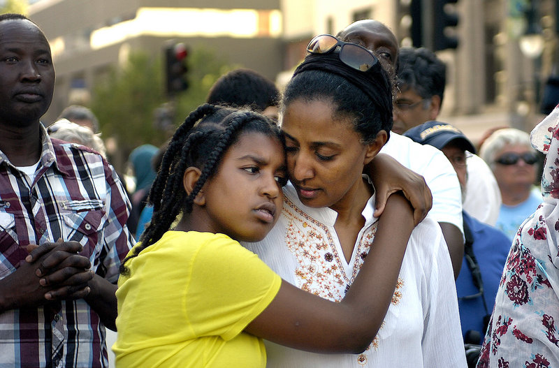 Wala Mohamed, left, in yellow shirt, hugs her mother, Abeir Ibrahim, of Portland, while attending a rally in Monument Square Monday, July 22, 2013, in memory of Trayvon Martin, the young black man who was killed last year in Florida. George Zimmerman, who stood trial for the killing, was found not guilty last week.