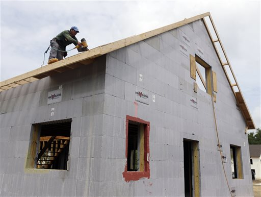 """A worker installs the roof of a zero net energy home in New Paltz, N.Y. The rafters will be heavily insulated and combined with castle-thick walls, insulated concrete slab below and triple-paned windows to create a """"building envelope"""" that makes each house nearly airtight before extra ventilation is installed."""