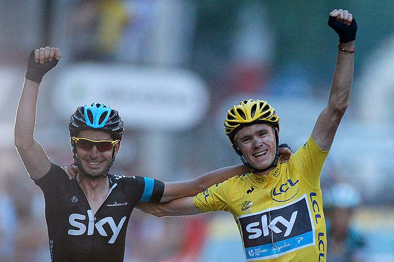 Chris Froome, wearing the overall leader's yellow jersey, crosses the finish line with a teammate in the last stage of the 100th edition of the Tour de France.