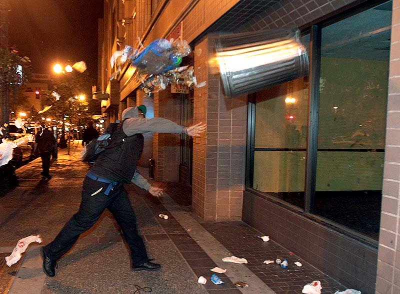 A man throws a trash can at the window of a building during a protest after George Zimmerman was found not guilty in the 2012 shooting death of teenager Trayvon Martin, early Sunday in Oakland, Calif. Protesters angered by the acquittal Zimmerman held largely peaceful demonstrations in three California cities, but broke windows and started small street fires Oakland, police said. ANDACHU 2013 EASTBAY southbay Protesters march in Oakland vandal