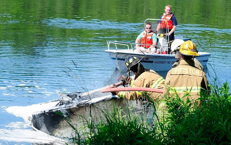 A Gardiner fireboat floats past as firefighters on shore spray foam on a burned boat on Friday, on the banks of the Kennebec River near Togus Stream in Pittston. Four people were on the boat when a fuel vapor explosion caused the fire, according to fire officials. The boat drifted down river from Gardiner landing to point where firefighters extinguished flames.