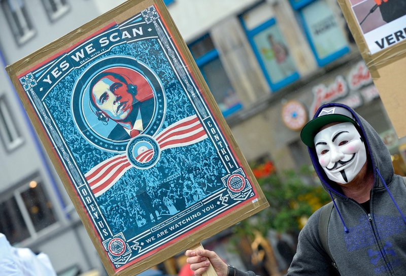 "A demonstrator protests with a poster against the National Security Agency Saturday in Hanover, Germany. Germany's top justice official says reports that U.S. intelligence bugged European Union offices remind her of ""the methods used by enemies during the Cold War."""