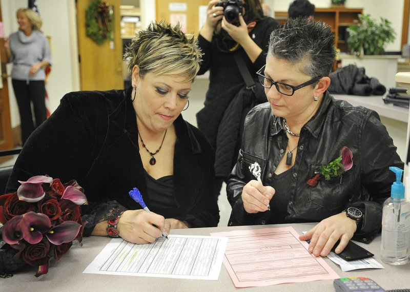 "Lisa Gorney, left, and Donna Galluzzo, both of Portland, sign their marriage license at Portland City Hall on Dec. 29, 2012. Legally married same-sex couples who want ""to fully claim first-class citizenship"" should call each other ""husband"" or ""wife,"" a reader says."