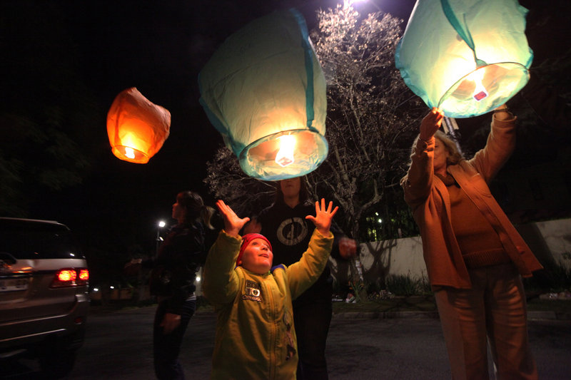 People light up and release lanterns outside Nelson Mandela's house in Johannesburg, South Africa, on Monday. Mandela remains in critical condition at a hospital in Pretoria.