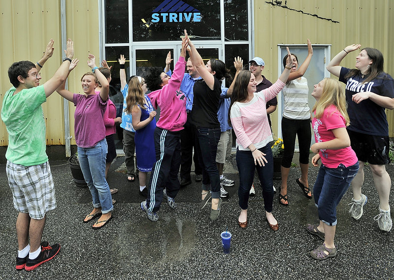 Members of STRIVE and staff practice their high fives outside their facility on Foden Road in South Portland on Tuesday, July 02, 2013,