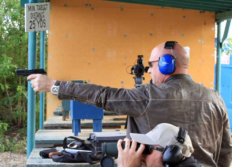Mark Kelly fires .22-caliber handgun at an Alaska shooting range on Tuesday. He and his wife, former U.S. Rep Gabrielle Giffords, met privately with 11 Alaska gun owners.