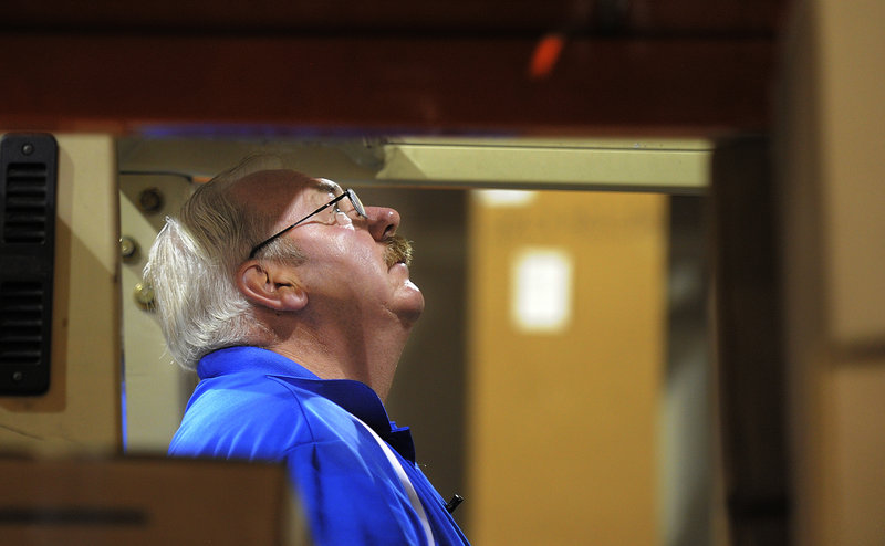 Bob Prescott looks up as he aligns his forklift at his new job for Distributor Corp. of New England in Westbrook. Prescott was laid off by Hostess late last year.