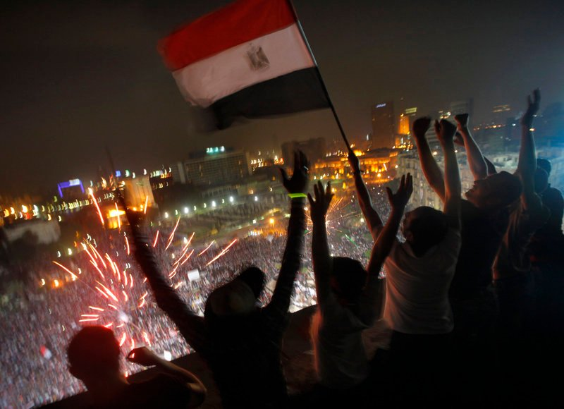 Fireworks go off in Cairo's Tahrir Square as Egyptians wave a flag in celebration of the ouster of their first democratically elected president.
