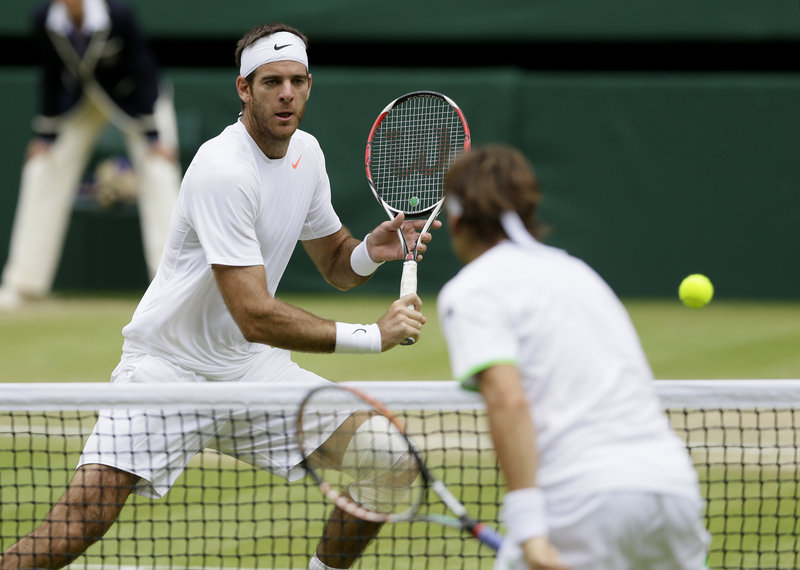 Juan Martin del Potro of Argentina, left, plays a return to David Ferrer of Spain during their Wimbledon quarterfinal. Del Potro will meet top-seeded Novak Djokovic after earning a straight-set victory.