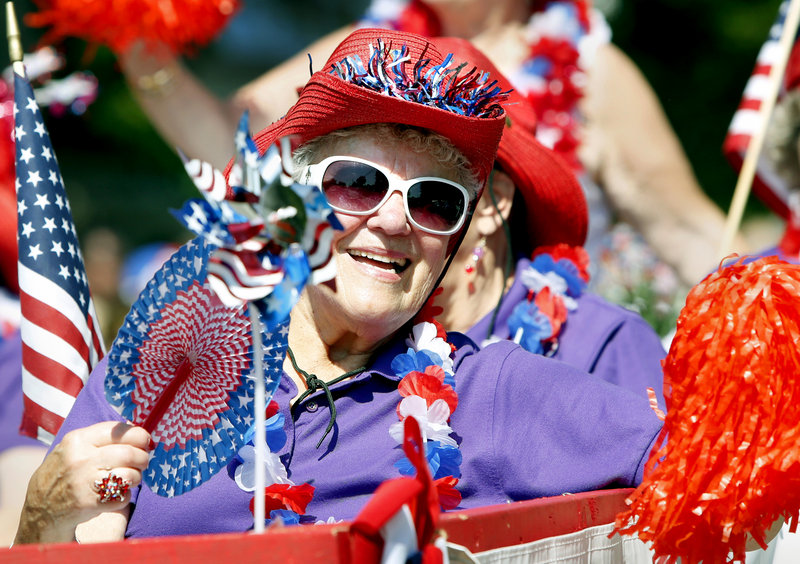 Janet Doherty of Old Orchard Beach waves to the crowd while riding on the Red Hat Society float during the 63rd Annual Independence Day Community Parade in Ocean Park.