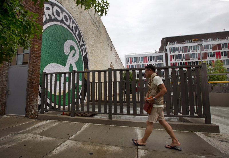 A modern apartment building stands in view of the Brooklyn Brewery, in Brooklyn, N.Y. The arrival of craft breweries can transform neighborhoods.