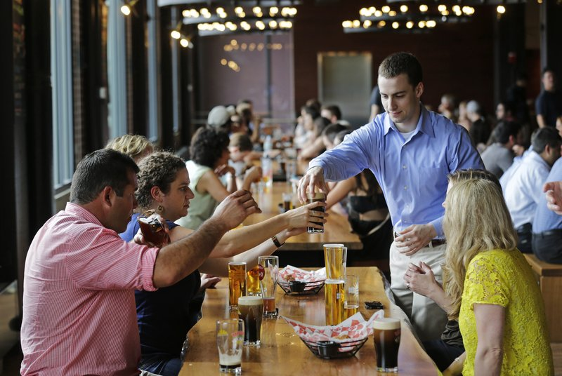 Customers sample a variety of beers at the Harpoon Brewery's Beer Hall in the Seaport District of Boston. The area is now attracting upscale businesses.