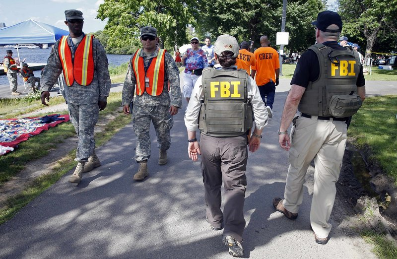 FBI agents and National Guard soldiers patrol along Boston's Esplanade Thursday. Amid high temperatures and heightened security, attendance appeared down at Boston's Fourth of July celebration, which included a performance by the Boston Pops Orchestra and a fireworks display. Organizers had instituted a series of new security measures this year in the wake of the April 15 Boston Marathon bombings. Authorities have said they believe the marathon bombing suspects initially planned to target the Independence Day event.