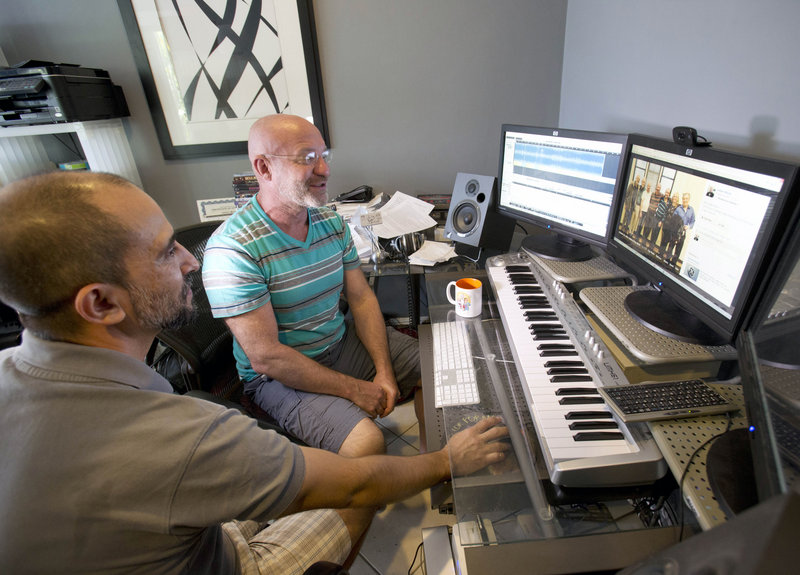 Tray Popov, left, and his husband, Julian Marsh, show their wedding photos on a computer in their Fort Lauderdale, Fla., home this week. Popov, a Bulgarian graduate student, and Marsh, a U.S. citizen, are the first gay couple in the nation to have their application for immigration benefits approved after the Supreme Court ruling on same-sex marriages, their lawyer said. Hundreds of federal benefits are still at stake for married gay couples in many states.